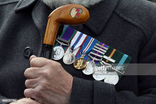 Former Ulster Defence Regiment soldier Tom Walker holds his engraved walking stick alongside his medals as Veterans of the Northern Ireland Troubles...