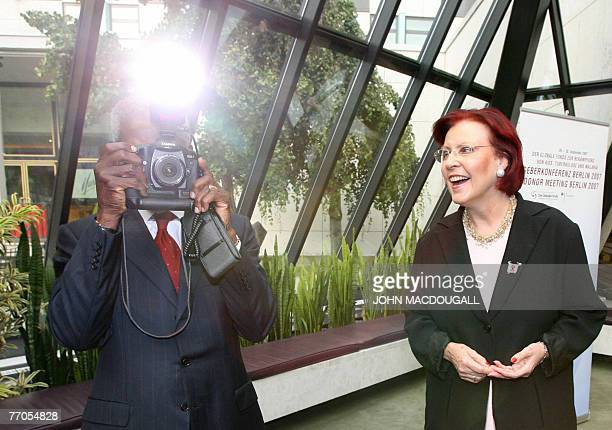 Former UN secretary general and Global Fund Replenishment Chair Kofi Annan takes pictures of press photographers as he waits with German Economic...