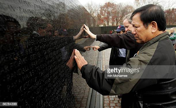 Former United States Marine Frank Corcoran a member of Veterans for Peace and Ho Sy Hai a veteran of the North Vietnamese Army search for names while...