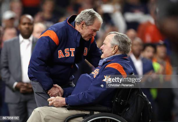 Former United States Presidents George HW Bush and George W Bush prepare to throw out the ceremonial first pitch before in game five of the 2017...