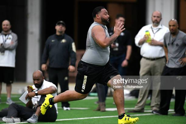 Former University of Colorado defensive tackle Josh Tupou runs a 40yard dash for NFL football scouts at the indoor practice field on the University...