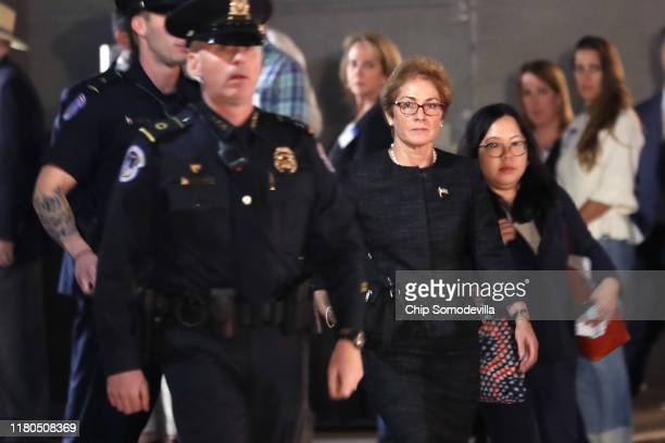 Former US Ambassador to Ukraine Marie Yovanovitch is surrounded by police aides and journalists as she departs the US Capitol October 11 2019 in...