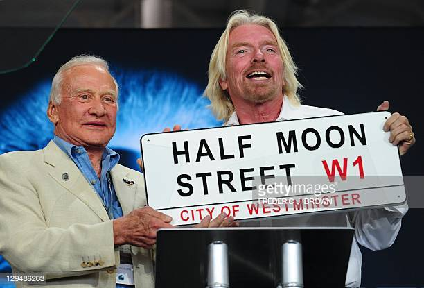 Former US Astronaut Buzz Aldrin presents Sir Richard Branson with a plaque from Virgin Galactic's London offices during a ceremony inside the hangar...