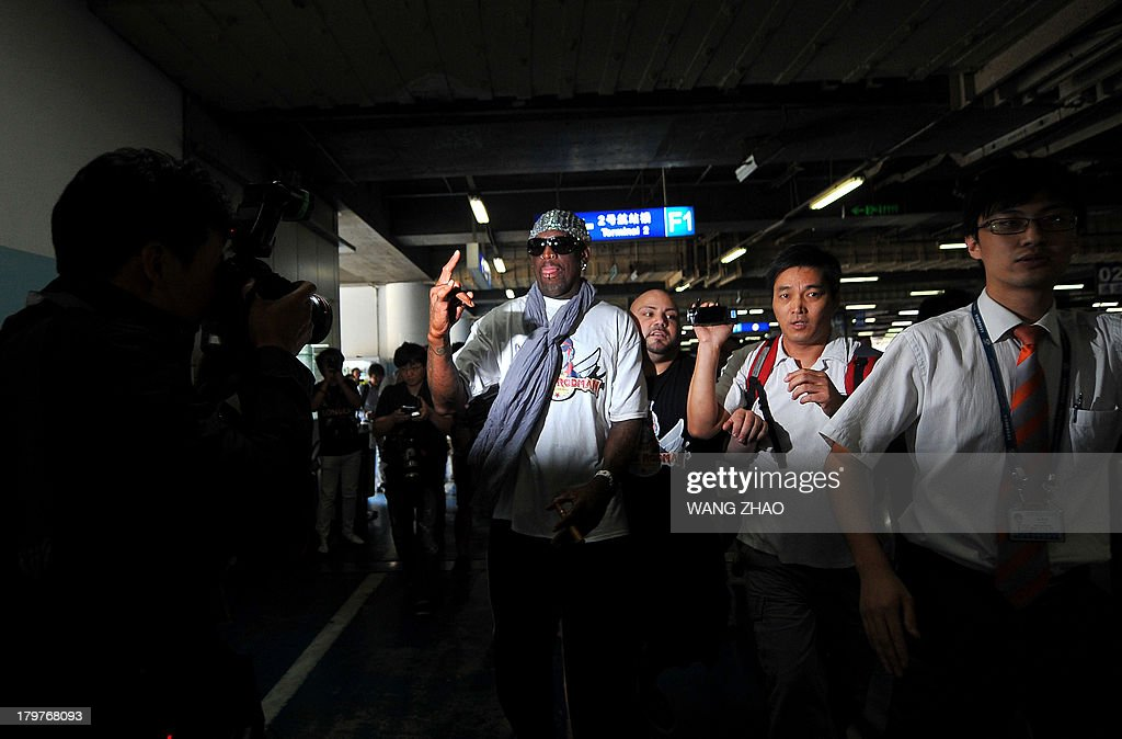 Former US basketball player Dennis Rodman (C) gestures to members of the media as he arrives at Beijing International Airport from North Korea on September 7, 2013. Rodman returned to China from Pyongyang on September 7 after a five-day trip when he met North Korean leader Kim Jong-Un, but without jailed American Kenneth Bae.