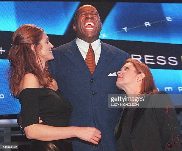 Former US basketball player Earvin Magic Johnson jokes with supermodel Cindy Crawford and actress Carrie Fisher as they host the Passport 99...
