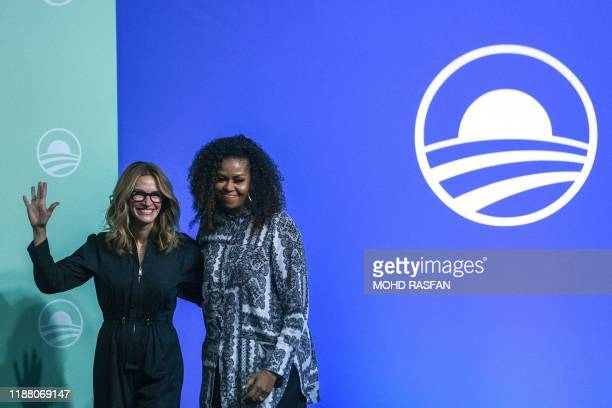 Former US first lady Michelle Obama and US actress Julia Roberts gesture as they arrive to attend an event for the Obama Foundation in Kuala Lumpur...