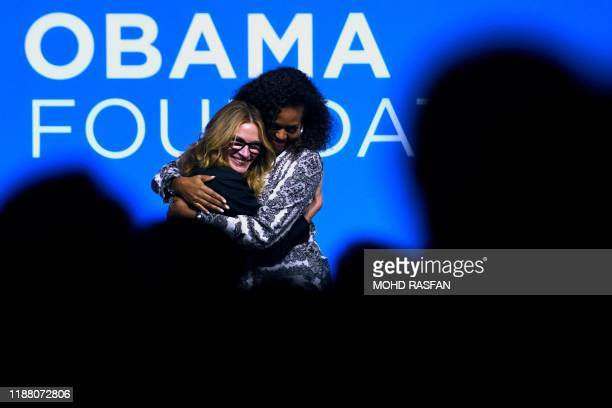 Former US first lady Michelle Obama and US actress Julia Roberts hug each other after attending an event for the Obama Foundation in Kuala Lumpur on...
