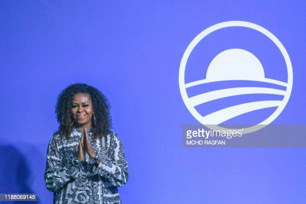 Former US first lady Michelle Obama gestures as she arrives to attend an event for the Obama Foundation in Kuala Lumpur on December 12, 2019.