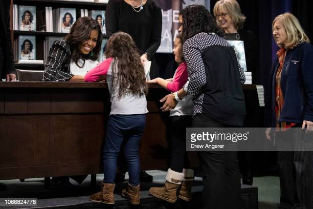 Former US First Lady Michelle Obama greets children as she signs copies of her new book 'Becoming' during a book signing event at a Barnes Noble...