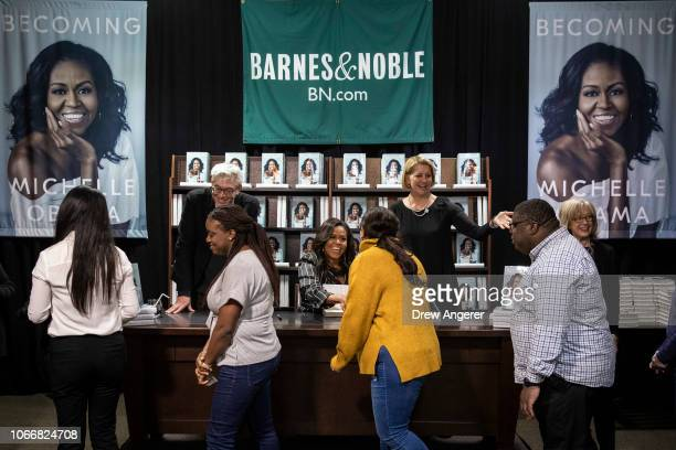 Former US First Lady Michelle Obama greets people as she signs copies of her new book 'Becoming' during a book signing event at a Barnes Noble...