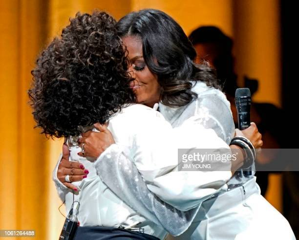 Former US first lady Michelle Obama hugs Oprah Winfrey at the opening of Obama's multicity book tour at the United Center in Chicago on November 13...