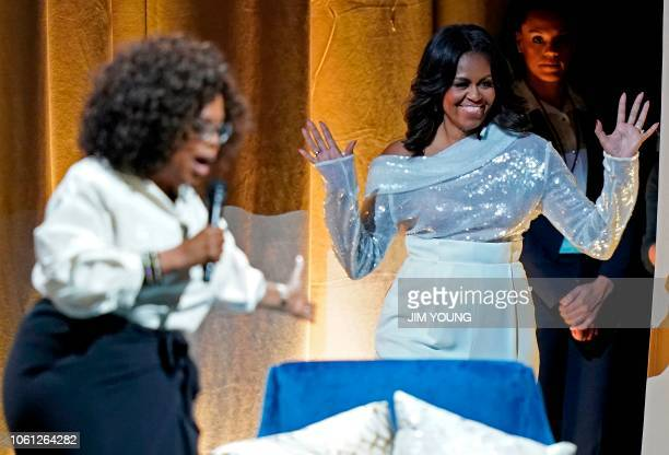 TOPSHOT Former US first lady Michelle Obama is introduced by Oprah Winfrey at the opening of her multicity book tour at the United Center in Chicago...