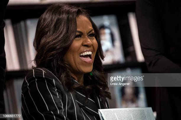Former US First Lady Michelle Obama laughs while signing copies of her new book 'Becoming' during a book signing event at a Barnes Noble bookstore...