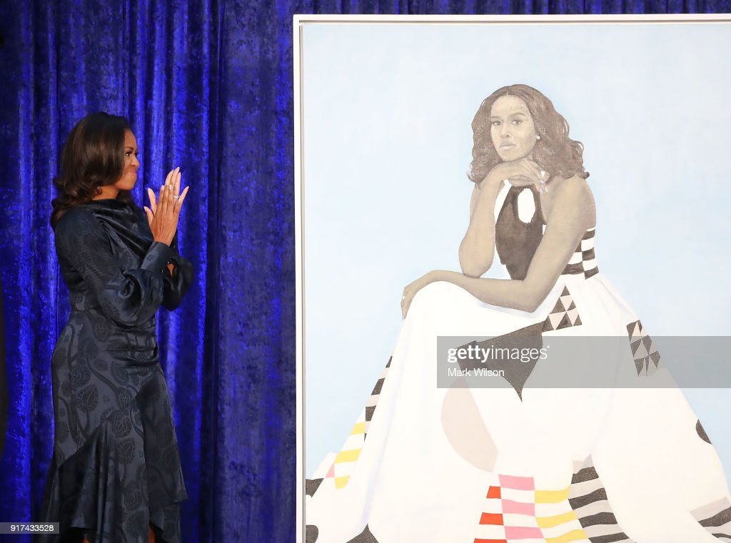 Former U.S. first lady Michelle Obama looks at her newly unveiled portrait during a ceremony at the Smithsonian's National Portrait Gallery, on February 12, 2018 in Washington, DC. The portraits were commissioned by the Gallery, for Kehinde Wiley to create President Obama's portrait, and Amy Sherald that of Michelle Obama.