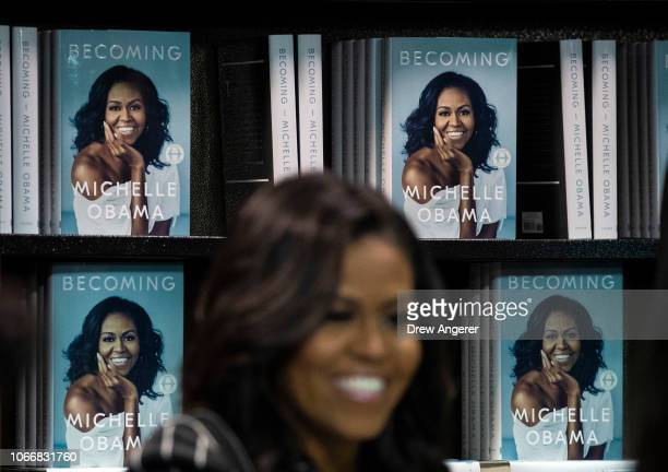 Former US First Lady Michelle Obama signs copies of her new book 'Becoming' during a book signing event at a Barnes Noble bookstore November 30 2018...