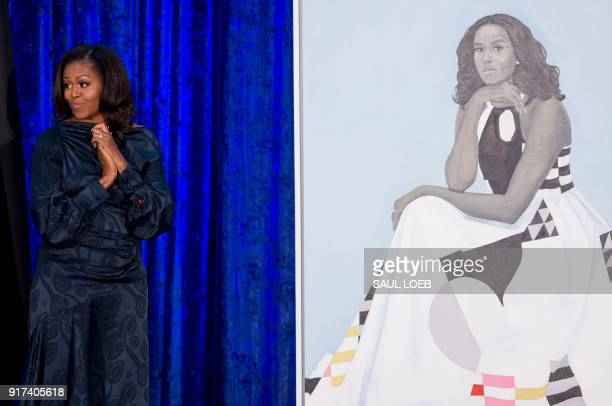 Former US First Lady Michelle Obama stands before her portrait by artist Amy Sherald after an unveiling at the Smithsonian's National Portrait...