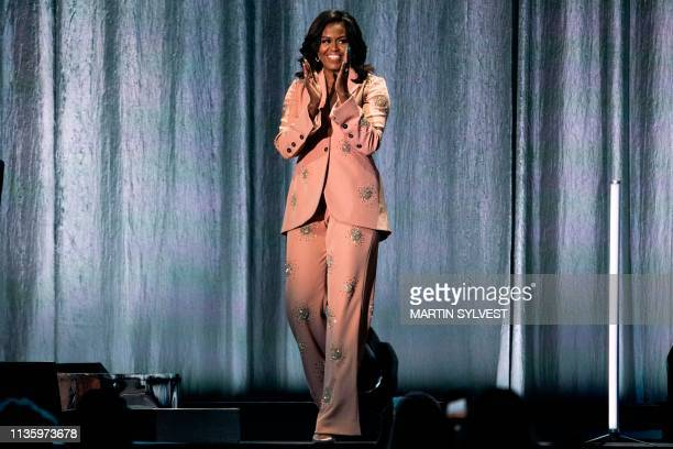 TOPSHOT Former US first lady Michelle Obama waves on stage of the Royal Arena in Copenhagen Denmark on April 9 during a tour to promote her memoir...