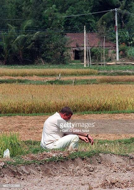Former US helicopter pilot Hugh Thompson who in 1968 tried to stop the My Lai massacre sits alone on a rice field in My Lai village central province...