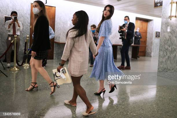 Former U.S. Olympic gymnasts McKayla Maroney and Simone Biles hold hands as they leave following their testimony before the Senate Judiciary...