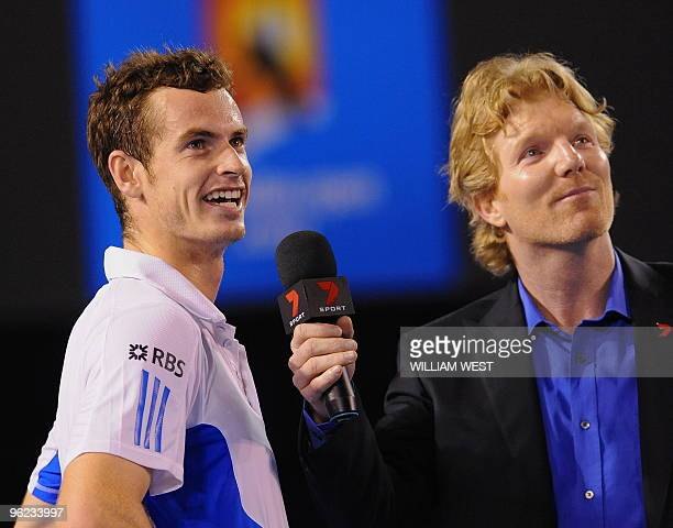 Former US player and current television commentator Jim Courier and winner Andy Murray of Britain looks up at a video screen to review highlights of...