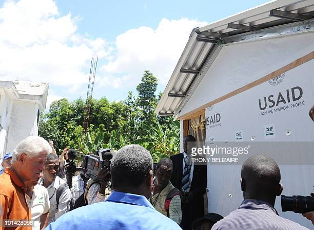 Former US president and special UN representative for Haiti Bill Clinton visits a construction project of small houses with Haitian Prime Minister...