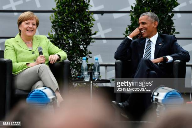 Former US president Barack Obama and Chancellor Angela Merkel laugh as they attend a panel discussion on stage during the Protestant church day event...