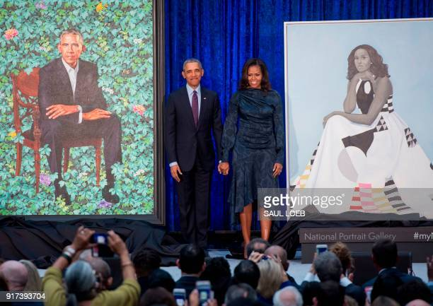 TOPSHOT Former US President Barack Obama and First Lady Michelle Obama stand beside their portraits after their unveiling at the Smithsonian's...
