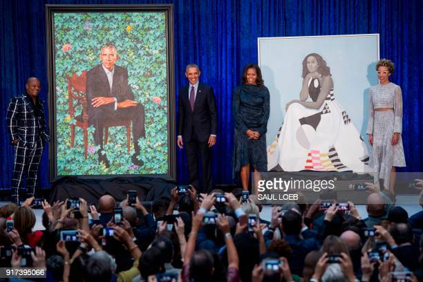 TOPSHOT Former US President Barack Obama and First Lady Michelle Obama stand before their portraits and respective artists Kehinde Wiley and Amy...