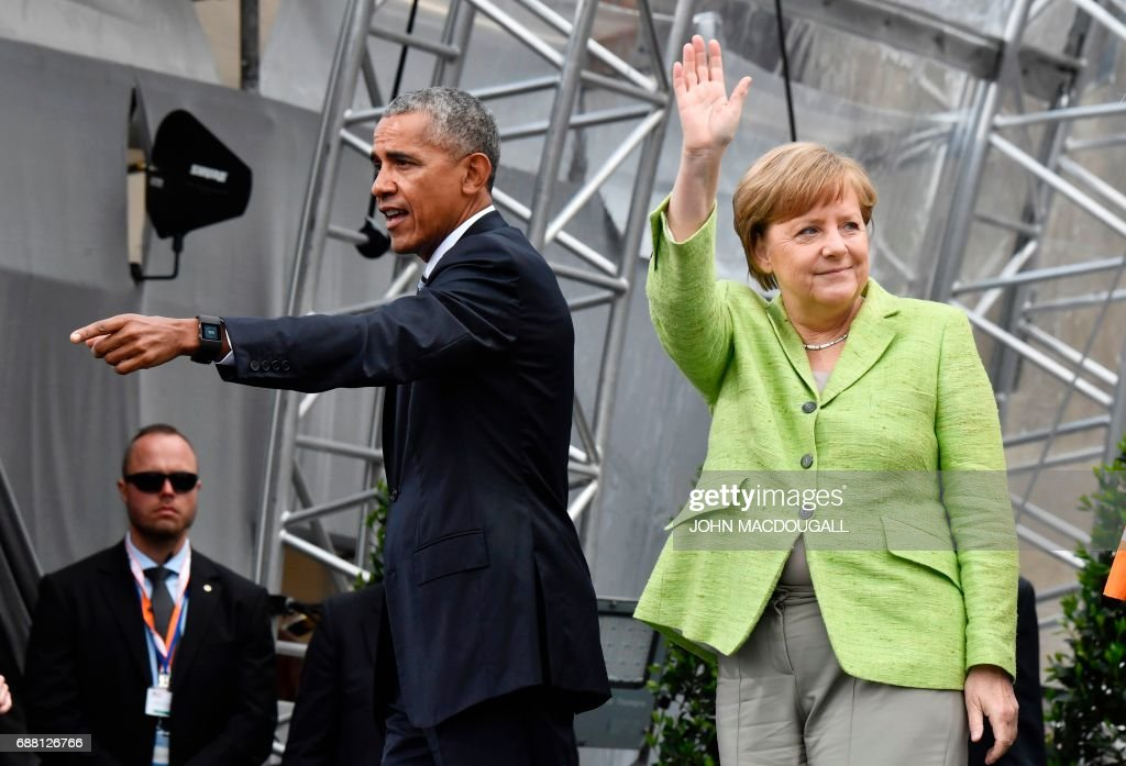 Former US president Barack Obama and German Chancellor Angela Merkel leave the stage after their panel discussion during the Protestant church day (Kirchentag) event at the Brandenburg Gate (Brandenburger Tor) in Berlin on May 25, 2017. ?Barack Obama attends a panel dicussion with Angela Merkel in Berlin before heading to Baden-Baden to receive a German media prize. / AFP PHOTO / John MACDOUGALL