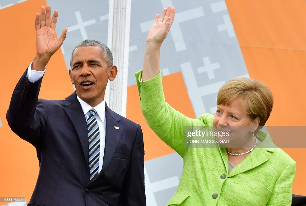 Former US president Barack Obama and German Chancellor Angela Merkel wave on stage ahead of a panel discussion during the Protestant church day (Kirchentag) event at the Brandenburg Gate (Brandenburger Tor) in Berlin on May 25, 2017. ?Barack Obama attends a panel dicussion with Angela Merkel in Berlin before heading to Baden-Baden to receive a German media prize. / AFP PHOTO / John MACDOUGALL / ALTERNATIVE