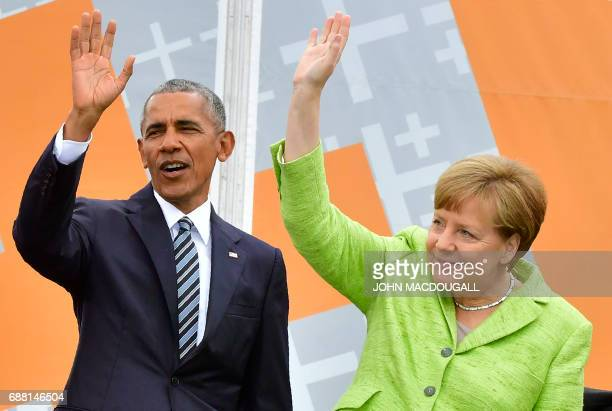 Former US president Barack Obama and German Chancellor Angela Merkel wave on stage ahead of a panel discussion during the Protestant church day event...