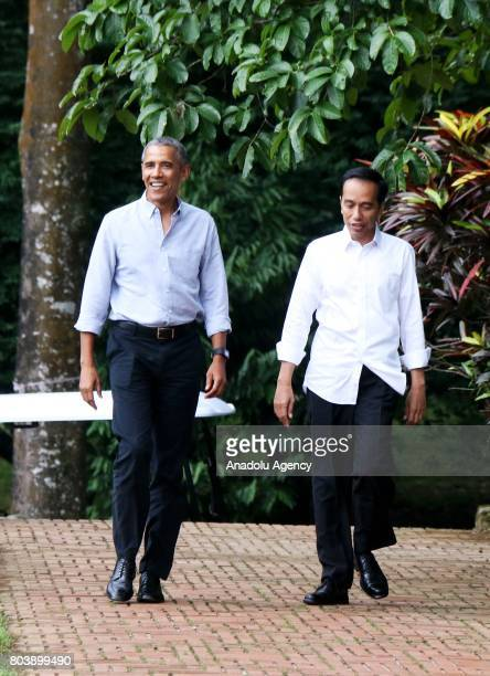 Former US President Barack Obama and Indonesian President Joko Widodo talk each other as they walk around Bogor Presidential Palace in Bogor West...