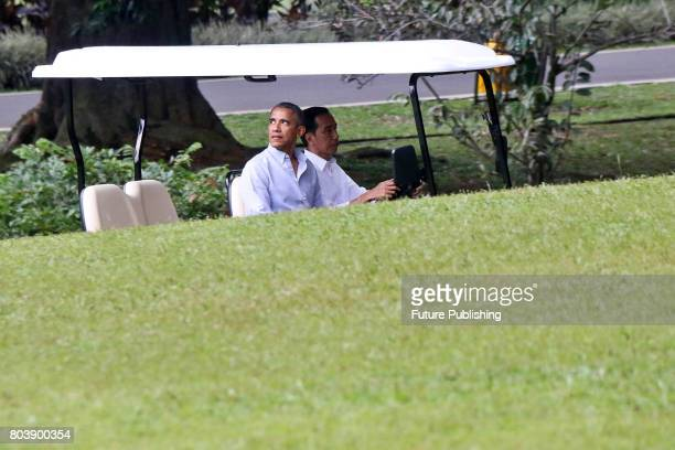 Former US President Barack Obama and Indonesian President Joko Widodo drive a golf cart as they leave Bogor Presidential Palace on June 30 2017 in...