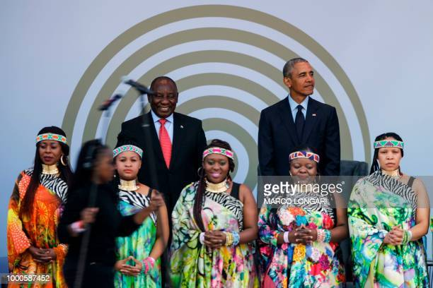 Former US President Barack Obama and South African President Cyril Ramaphosa stand on stage behind the Soweto Gospel Choir during the 2018 Nelson...