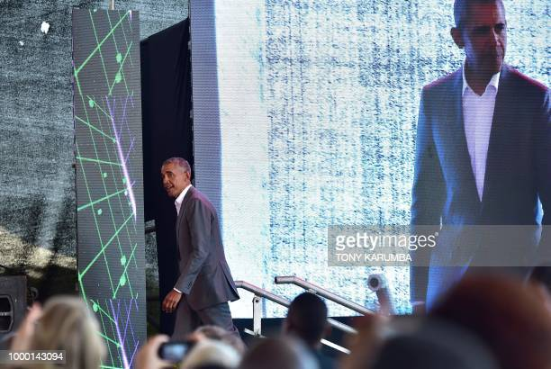 Former US President Barack Obama arrives on stage to make an address on July 16 2018 in front of a projected backdrop during the opening of the Sauti...