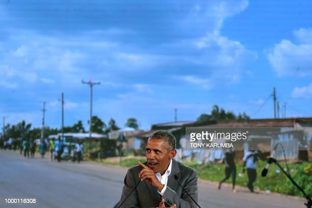 Former US President Barack Obama gestures as he makes an address on July 16 2018 in front of a projected backdrop showing a view of his father's home...
