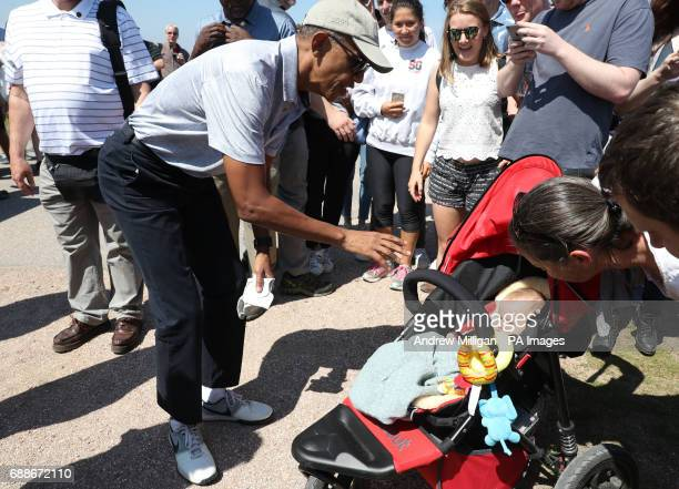 Former US president Barack Obama is introduced to a baby during his visit to the Old Course in St Andrews Fife where he played a round of golf