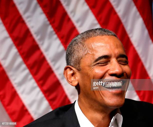 Former US President Barack Obama laughs during a forum with young leaders to discuss community organizing an at the University of Chicago in Chicago...
