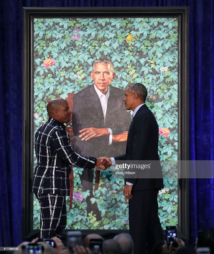 Former U.S. President Barack Obama stands artist Kehinde Wiley next to his newly unveiled portrait during a ceremony at the Smithsonian's National Portrait Gallery, on February 12, 2018 in Washington, DC. The portraits were commissioned by the Gallery, for Kehinde Wiley to create President Obama's portrait, and Amy Sherald that of Michelle Obama.