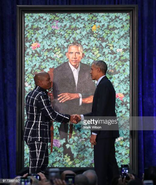 Former US President Barack Obama stands artist Kehinde Wiley next to his newly unveiled portrait during a ceremony at the Smithsonian's National...