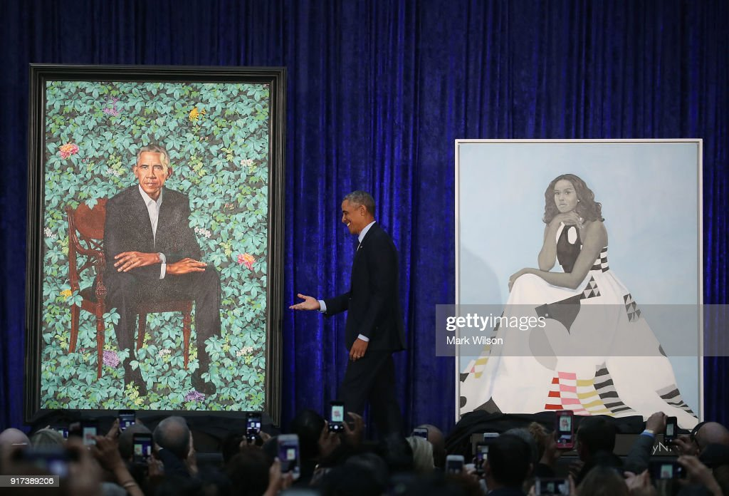 Former U.S. President Barack Obama stands with his and former first lady Michelle Obama's newly unveiled portrait during a ceremony at the Smithsonian's National Portrait Gallery, on February 12, 2018 in Washington, DC. The portraits were commissioned by the Gallery, for Kehinde Wiley to create President Obama's portrait, and Amy Sherald that of Michelle Obama.
