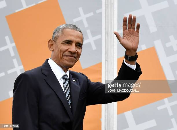 Former US president Barack Obama waves as he arrives on stage before attending a discussion with the German Chancellor during the Protestant church...