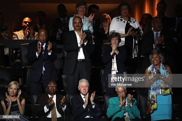 Former US President Bill Clinton and Former attorney general Eric Holder clap while listening to first lady Michelle Obama deliver remarks on the...