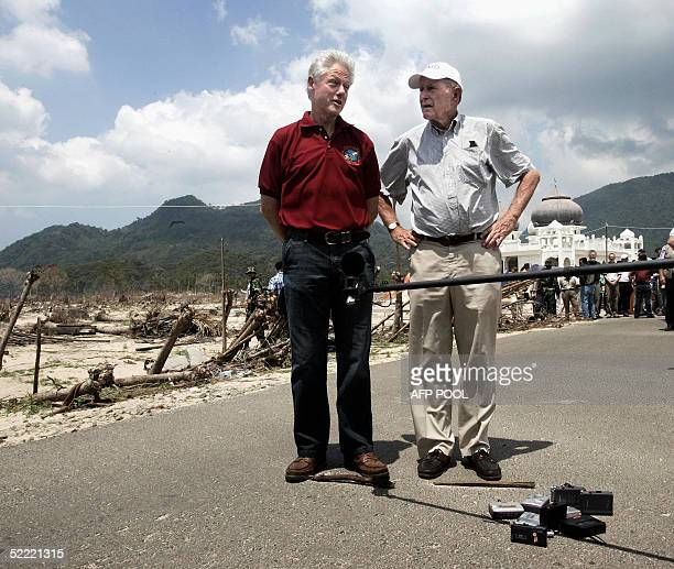 Former US President Bill Clinton and George HW Bush talk to the press in the devastated town of Lampuuk Aceh province 20 February 2004 during their...