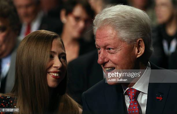 Former US president Bill Clinton and his daughter Chelsea Clinton look on before the start of the third US presidential debate with republican...