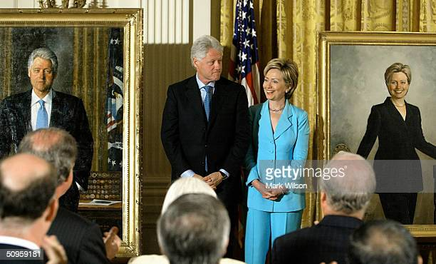 Former US President Bill Clinton and his wife US Senator Hillary Clinton look at the newly unveiled Clinton portraits in the East Room of the White...