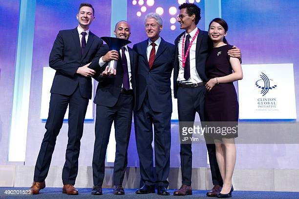 Former US President Bill Clinton and the winning team IMPCT attend the Hult Prize Award Dinner during the first day of the 2015 Clinton Global...