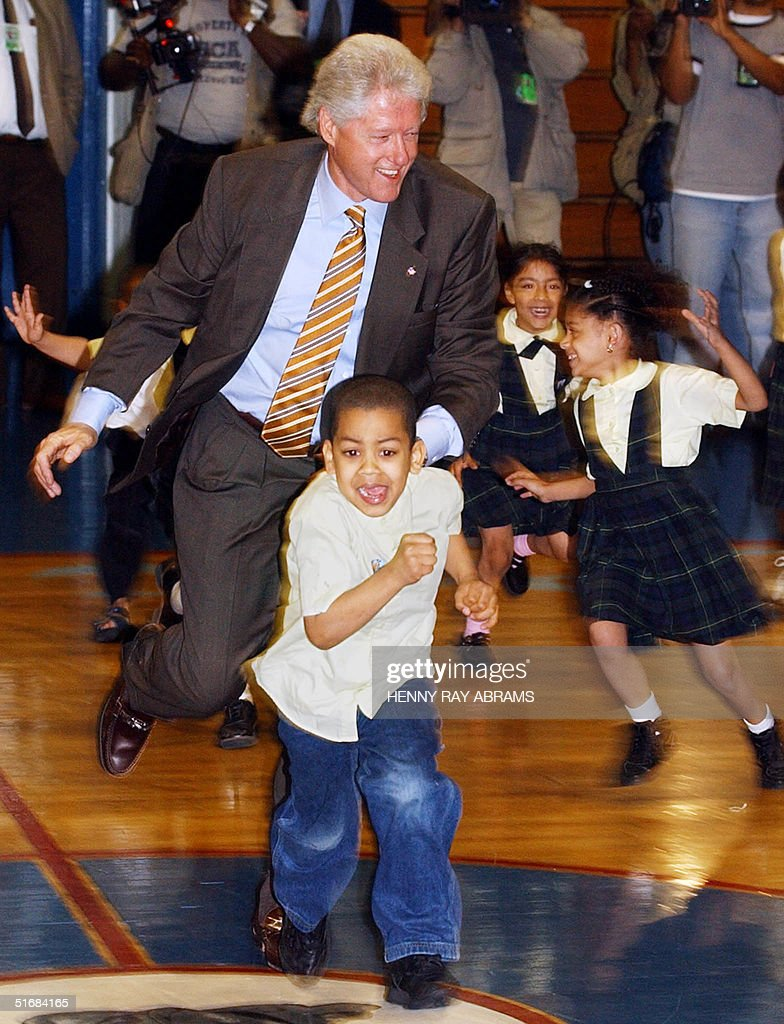 Former US President Bill Clinton chases a group of students from the Family Life Academy of the Latino Pastoral Action Center during a game of 'The Chicken and the Fox' 20 June, 2002. President Clinton, who played the fox, visited the Bronx facility as part of the Democratic Leadership Council's 'National Service Day,' a day on which elected officials draw attention to the promise of national service. AFP PHOTO/ Henny Ray ABRAMS