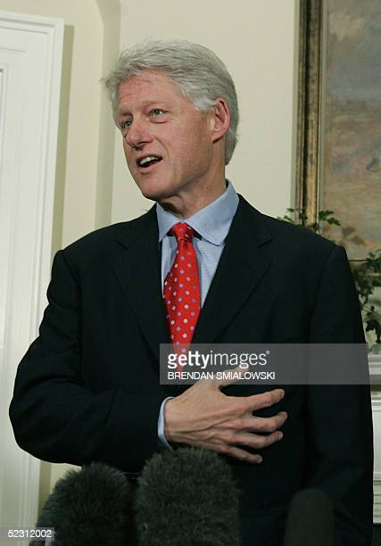 Former US President Bill Clinton gestures to his heart while discussing his health in the Roosevelt Room of the White House 08 March 2005 in...