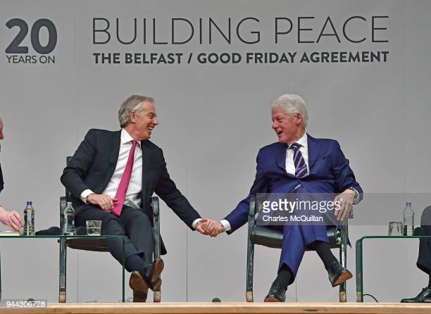 Former US President Bill Clinton holds hands with former British Prime Minister Tony Blair as they attend an event to mark the 20th anniversary of...